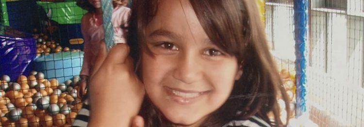 Elham som barn, der smiler til kameraet. Hun leger i et legeland.