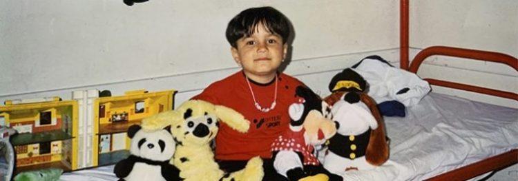 Elham som lille. Hun sidder på sin seng i asylcenteret med fire bamser.