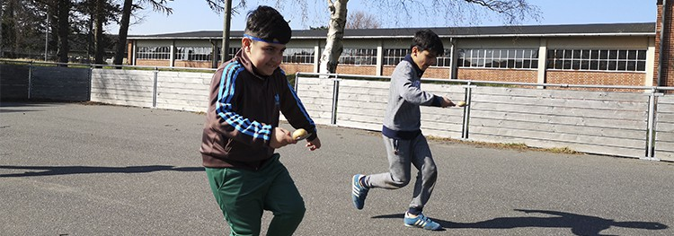 Yousef og en anden dreng løber om kap imens de ballancerer et æg på en spiseske.