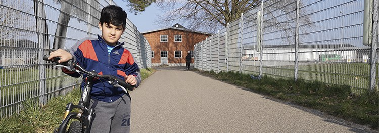 Younes står med sin cykel på Sjælsmark ved et metalhegn. I baggrunden ser man en rød bygning.
